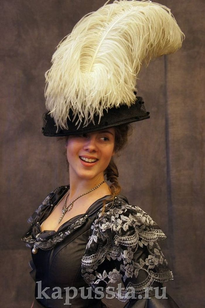 A dark gray dress with a hat and feathers